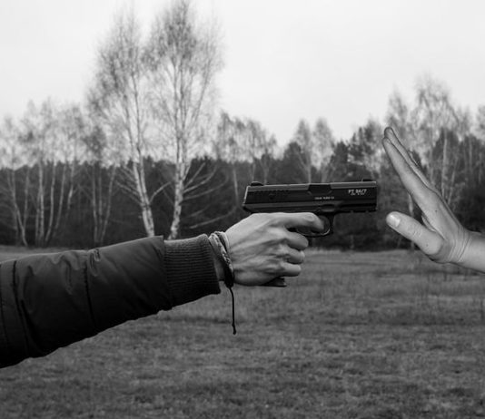 hand holding a gun and pointing it to someone