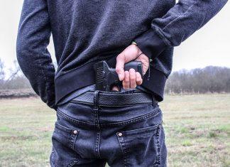crime suspect hiding a gun at his back